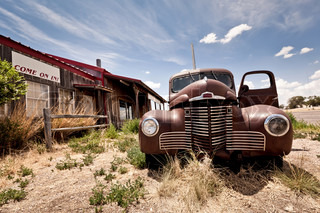 Abandoned restaraunt and old style car near gas station on the famous route 66 road in USA