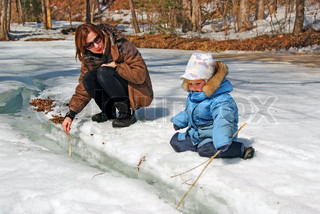 family of mother with kid playing in the snow spring forest stream