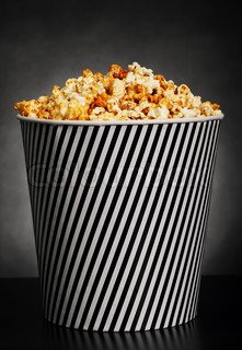 Popcorn in a container on black background