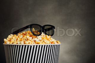 Popcorn in a box with HD cinema glasses on black background