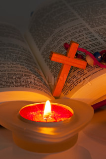 Open Bible with cross and burning candles