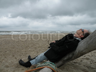 man relaxing on a tree at the beach on a windy day