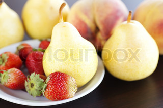 strawberry  in plate, pear and peach on a wooden table