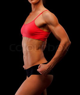 Muscular female body against black background