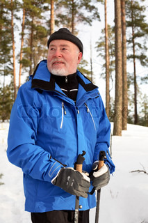 senior man with nordic walking sticks enjoying sunny morning in snowy forest