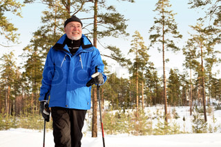 happily smiling senior man nordic walking in forest in sunshine