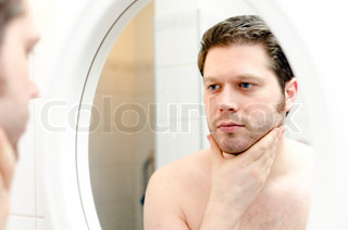 Man looks at his beard and thought about shaving