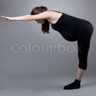 Pregnant woman doing gymnastic exercises on grey background