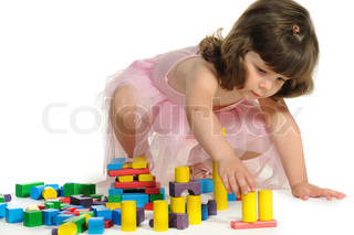 The lovely little girl plays colour wooden cubes