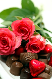 close-up of pink roses, chocolate pralines and a red heart-shaped one
