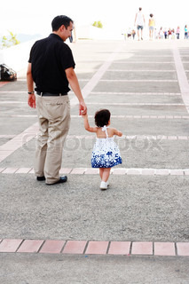 Baby walking like a model with her father