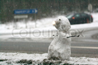 A dirty snowman crossing the road