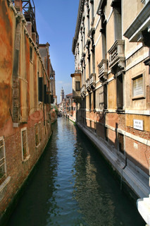 Vertical oriented image of small narrow canal among historic building in Venice, Italy.