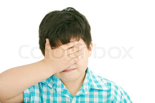 portrait of sad crying little boy covers his face with her hand