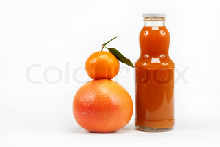 Juice in a glass bottle and tropical fruits on a white background