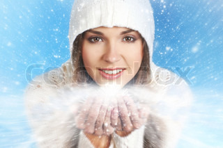 Portrait of young and attractive girl in Christmas style over winter background
