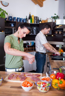 Young couple working in kitchen