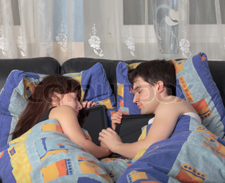 Young couple asleep with a tablet laptop