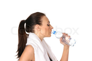 Young attractive female sportsman drinking water