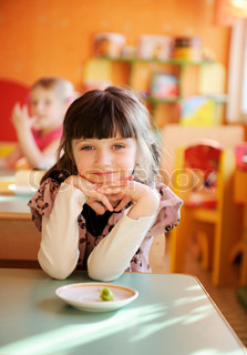Happy little girl sitting at a table