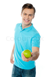 Good looking healthy guy offering a green apple