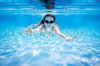 Woman swimming underwater in pool Summer vacations
