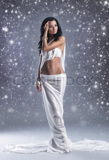 Fashion shoot of Aphrodite styled young woman over winter background with snow
