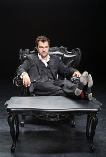man in a suit sitting in a chair with his feet on the desk