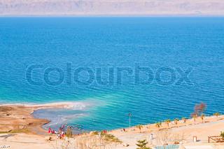people on sand beach of Dead Sea