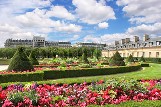 View on beautiful park at Les Invalides with red flowers and green lawns under blue sky with white clouds in Paris, France.