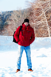 young guy in a red jacket on the background of the snow forest