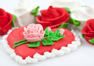 Cake with roses in heart shape on white background.