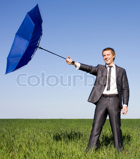 Businessman in the field carries a strong wind