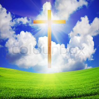 shiny wooden easter cross over green field and blue sky with sun rays
