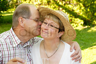 loving mid-adult married couple hugging and kissing in garden