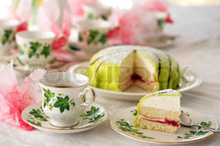 slice of delicate princess cake and vintage coffee cup in foreground of laid coffee table