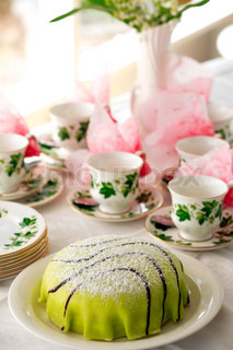 close-up of princess cake in front of set of old coffee cups, shallow DOF
