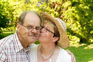 happy mid-adult married couple hugging and kissing in garden