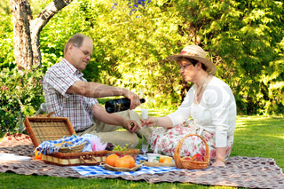 mid-adult couple having picnic in garden drinking sparkling wine