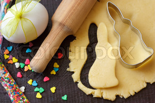 Easter bunny cookies, rolling pin and egg with ribbon on an old wooden table