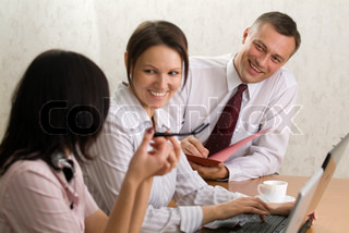 Smiling chief with a folder and two beautiful office girls with a laptop