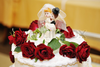 Figurines on top of wedding cake with real roses decorations