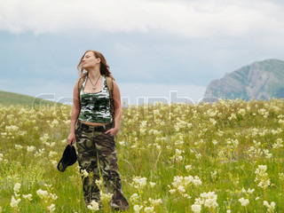 Girl has stopped to take pleasure in a warm wind blowing high in mountains
