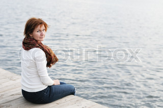 Middle age woman sitting on wood boards by the water