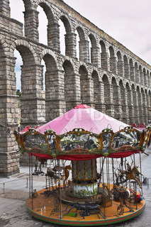 Children's roundabout and ancient aqueduct on the area of Segovia