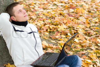 guy with laptop at tree