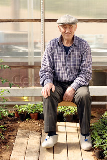 old farmer sitting in his home made greenhouse where growing oa flower plants