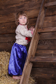 young cute child in traditional eastern european clothes on hayloft