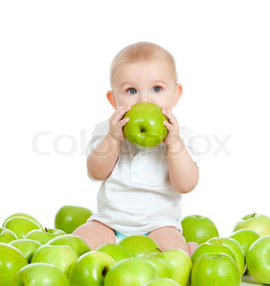 Adorable baby sitting among fresh fruits and eating green apple