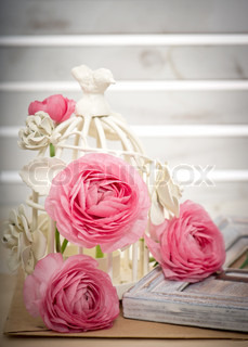 pink ranunculus flowers with decorative bird cage